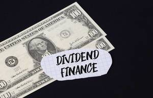 """""""Dividend finance"""" Text auf kariertem Zettel mit zwei 100-Dollar-Scheinen vor schwarzem Hintergrund"""