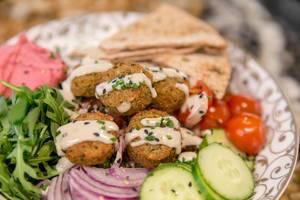 """Falafel Bowl"" im Fit Kitchen mit Tahini, Tsatsiki, Fetakäse, Tabouleh, Kalamata-Oliven, Spinat und Pitabrot, in Barcelona, Spanien"
