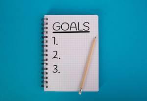 """""""Goals"""" - Ziele - mit drei freien Punkten für eine Auflistung, auf einem Karoblock mit Bleistift, vor blauem Hintergrund"""