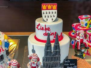 """Love your city / Liebe deine Stadt"": cake celebrating the city of Cologne with the cathedral and the emblem of the city, surrounded by typical decoration of the city"