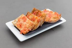 """""""Pan de cristal con tomate"""" ist ein dünnes Brot mit Tomatenaufstrich im Restaurant des Hotel 1898, auf einem weißen Teller in Barcelona, Spanien"""