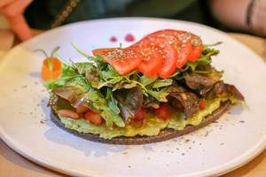 """""""Petit Pa with tomatoes"""" is a raw bread made wit sunflower and flax seeds, green leaves topping and avocado at Petit Brot in Barcelona, Spain"""