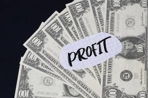 """""""Profit"""" Text auf kariertem Zettel mit 100-Dollar-Scheinen"""