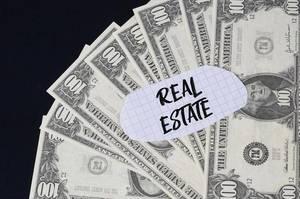 """""""Real estate"""" Text auf kariertem Zettel mit 100-Dollar-Scheinen"""