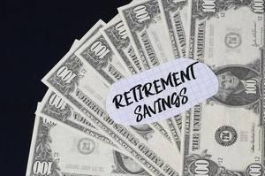 """""""Retirement savings"""" Text auf kariertem Zettel mit 100-Dollar-Scheinen"""