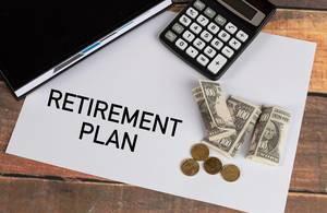 """""""Ruhestands-Plan""""  auf Papier geschrieben, neben einem schwarzem Notizbuch, Taschenrechner und wenig Geld"""