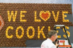 """We love Cookies"" - wall lettering made off brown and yellow cookies at anuga food fair in Germany"