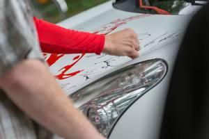 1. FC Köln Spieler signiert ein Auto