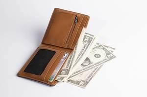 100-Dollar Banknoten fallen aus geöffneter Brieftasche aus braunem Leder vor weißem Hintergrund