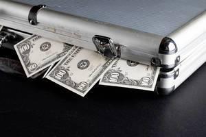 100 Dollar Noten gucken aus einem Geldkoffer heraus