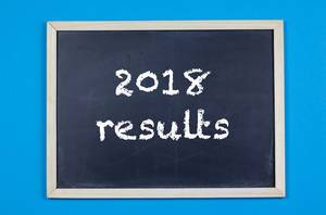 2018 results written on a black chalkboard on blue background