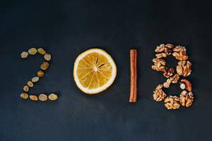 2018 symbolised by an orange, nuts and cinammon as the winter ingredients on black background