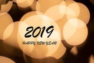 2019 HAPPY NEW YEAR Wunsch in hellen Lichterkegeln vor schwarzem Hintergrund