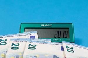 2019 steht auf dem Display eines Sharp Taschenrechners mit Geldscheinen auf blauem Hintergrund