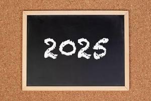 2025 auf einer schwarzen, gerahmten Tafel geschrieben