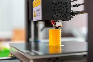 3D printer printing a yellow piece