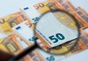 50 € Bills on a white background and with and a magnifier glass