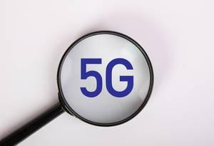 5G in blauer Schrift auf weiß, vergrößert dargestellt unter einer Lupe