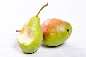 A bitten pear and a whole pear on a white wooden background