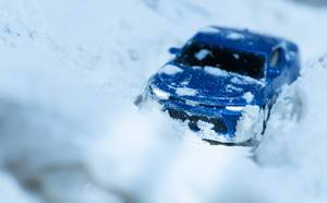 A blue car buried in a snowdrift with lights on