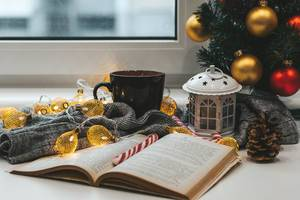 A book with a Christmas tree, a cup of tea and garlands on a background of a window. Winter home relaxation concept