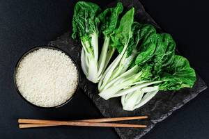 A bowl of rice, chopsticks and cabbage Pak Choi baby on a black background, top view