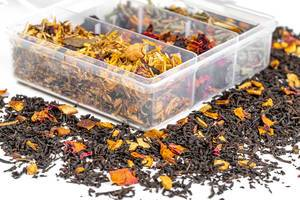 A box with different types of tea and scattered dry tea on a white background