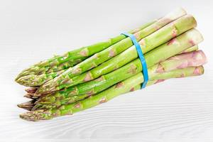 A-bunch-of-fresh-asparagus-on-a-white-wooden-table.jpg