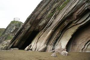 A cave on the beach of Zumaia, with earth layers of Flysh, in Basque country Spain