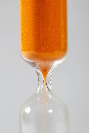A closeup of an hourglass with falling sand on a white background
