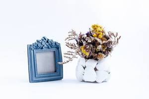 A composition with vintage photo frame and vase with dry flowers