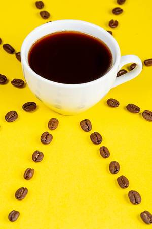 A Cup of fresh coffee on a yellow background and coffee beans