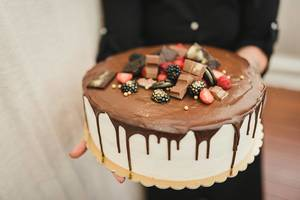 A Delicious White Chocolate Cake In Woman