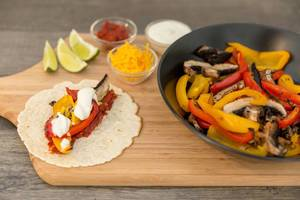 A fajita with hot tomato sauce, peppers, mushrooms, cheddar cheese and cream with lime on a wooden cutting board next to a black bowl
