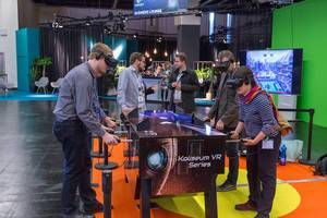 A few persons playing virtual table football Koliseum VR Series with VR glasses