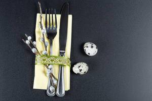 A fork and knife with a yellow napkin , willow branches and quail eggs on a black background. The concept of preparation for Easter (Flip 2020)