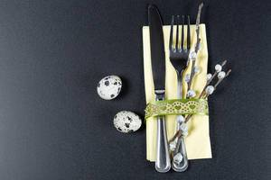 A-fork-and-knife-with-a-yellow-napkin-willow-branches-and-quail-eggs-on-a-black-background-the-concept-of-preparation-for-Easter.jpg