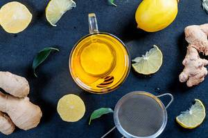 A glass cup of tea surrounded by lemons, ginger root, leaves and tea strainer