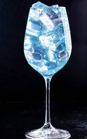 A glass filled with a blue cocktail with ice on black background (Flip 2019)