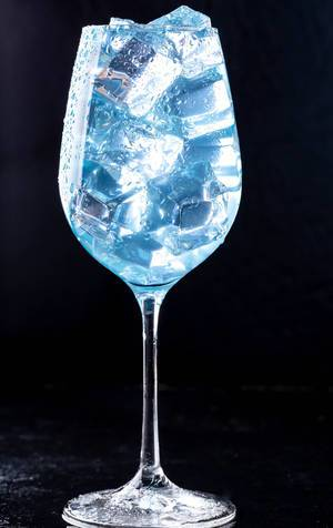 A glass filled with a blue cocktail with ice on black background