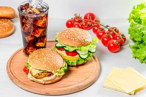 A glass of Cola with ice and fresh burgers on a round kitchen Board (Flip 2019)