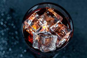 A glass of cold Cola with ice on a black background with water drops