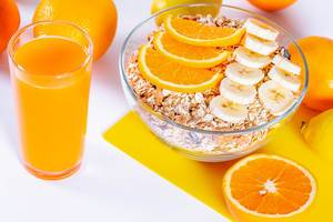 A glass of fresh orange juice and a bowl of dietary porridge with oranges and bananas