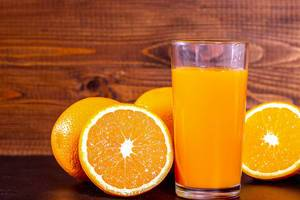 A glass of fresh orange juice with fruit oranges