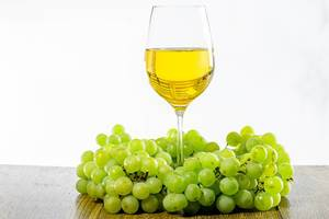 A glass of white wine surrounded by bunches of green grapes (Flip 2019)