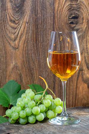 A glass of wine and a bunch of grapes on a wooden background (Flip 2019)