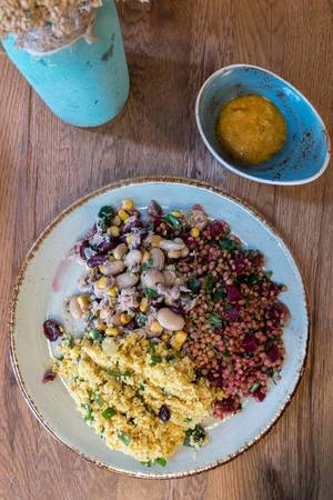 A healthy vegan meal - couscous with lentils and beetroots with a salat from white beans, tuna and sweet corn
