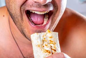 A hungry man with an open mouth and a shawarma in hand (Flip 2019)