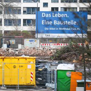 "A large construction site in front of a building with a sign in German ""Life is a construction site"" taken from the Bible"