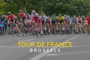 "A large group of cyclists at the world famous cycling race, next to the text ""Tour de France Brussels""."
